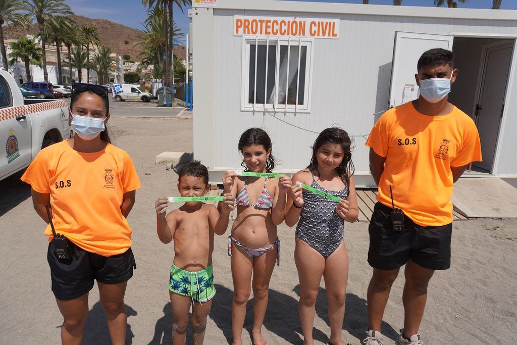 Miembros de protección civil con los niños con sus pulseras en Carboneras, Almería.