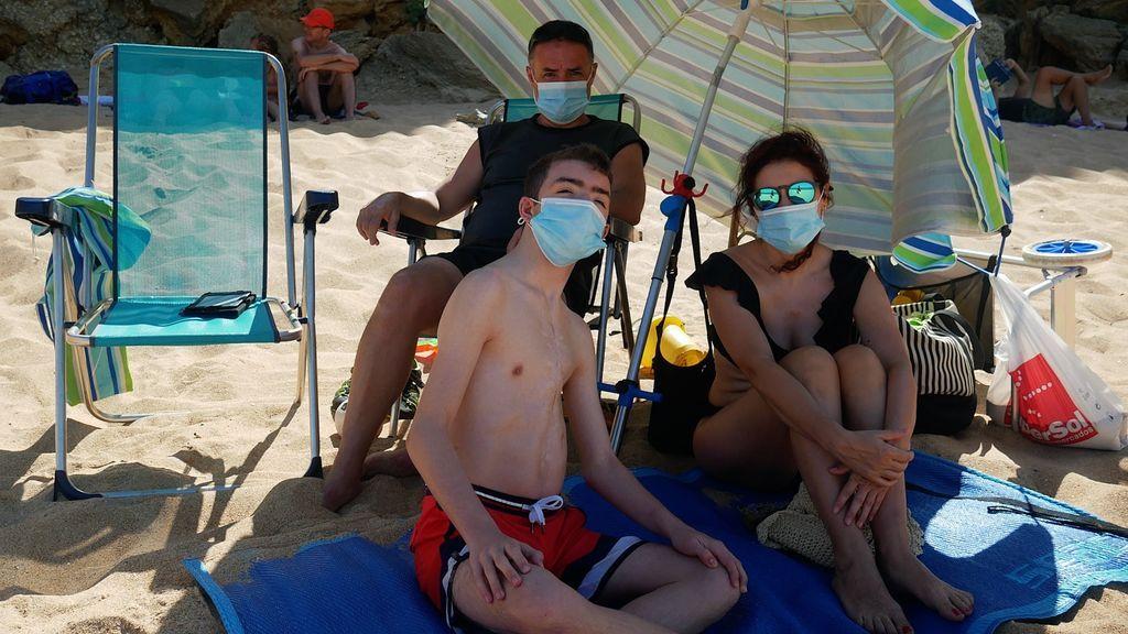 Una familia en la playa, con sus mascarillas
