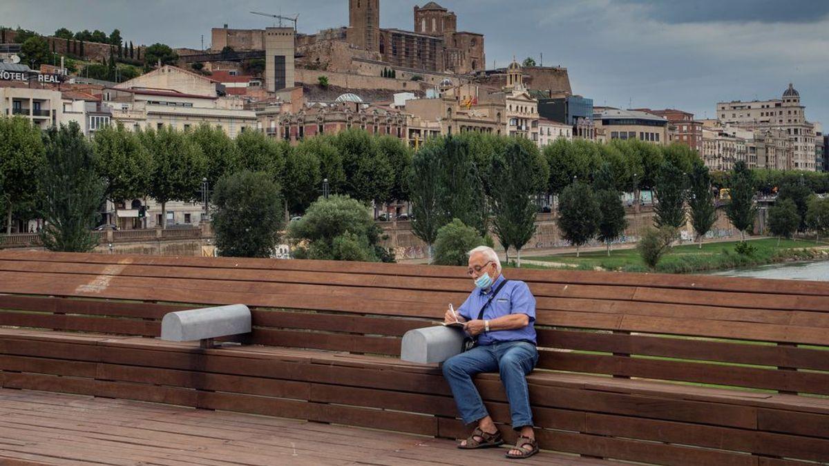 Un hombre ataviado con una mascarilla descansa en un banco de Lleida