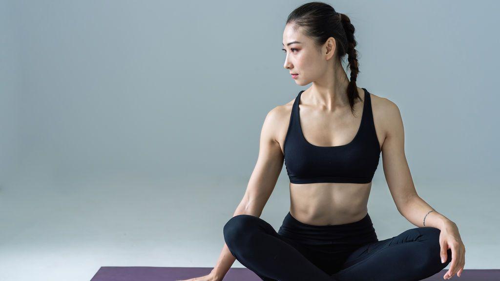 woman-sitting-on-yoga-mat-2294352