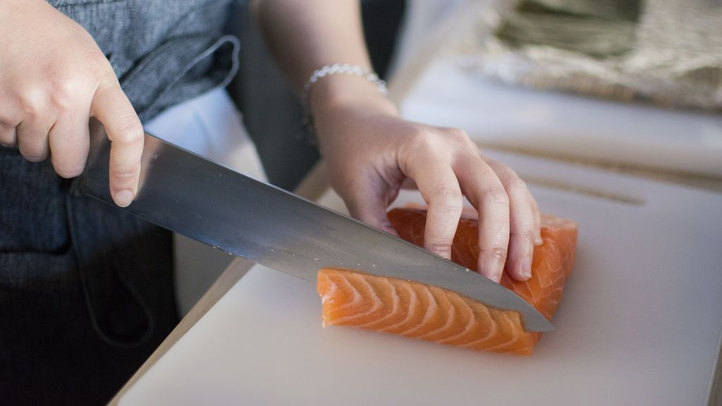 person-slicing-meat-on-white-chopping-board-1409050