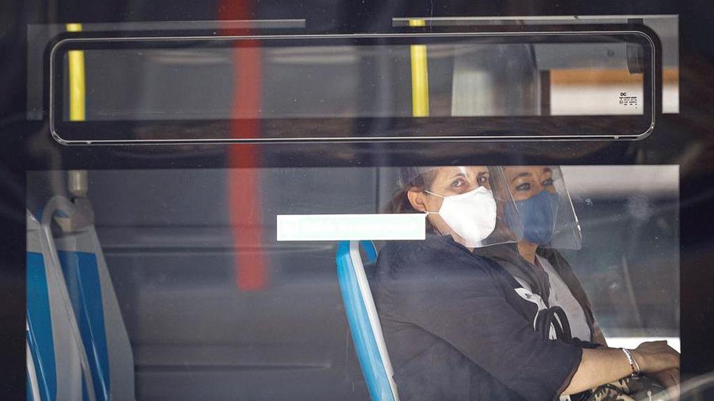 Dos mujeres con mascarilla y pantalla se sientan al lado en un autobús de la EMT en Madrid