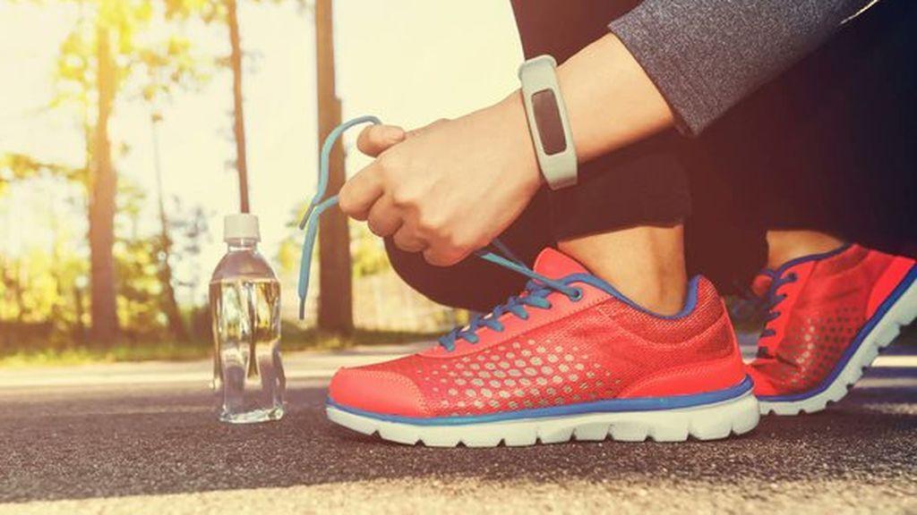 persona atando los cordones de unas zapatillas para correr