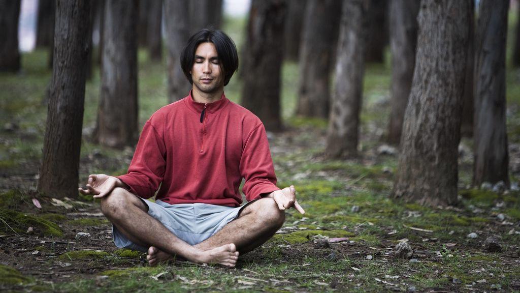 persona practicando mantras de yoga en el bosque