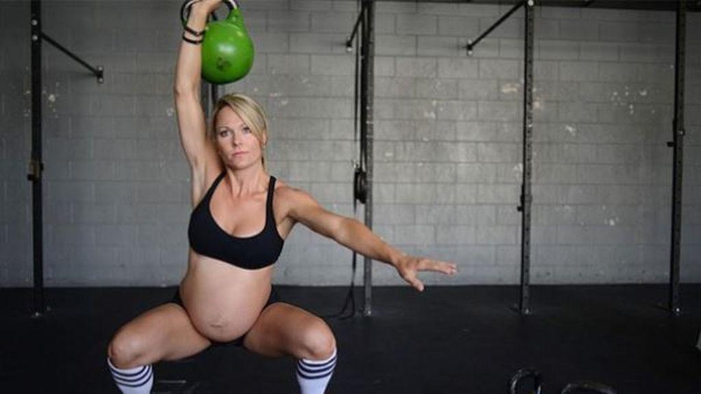 mujer embarazada realizando un ejercicio de crossfit con pesa rusa
