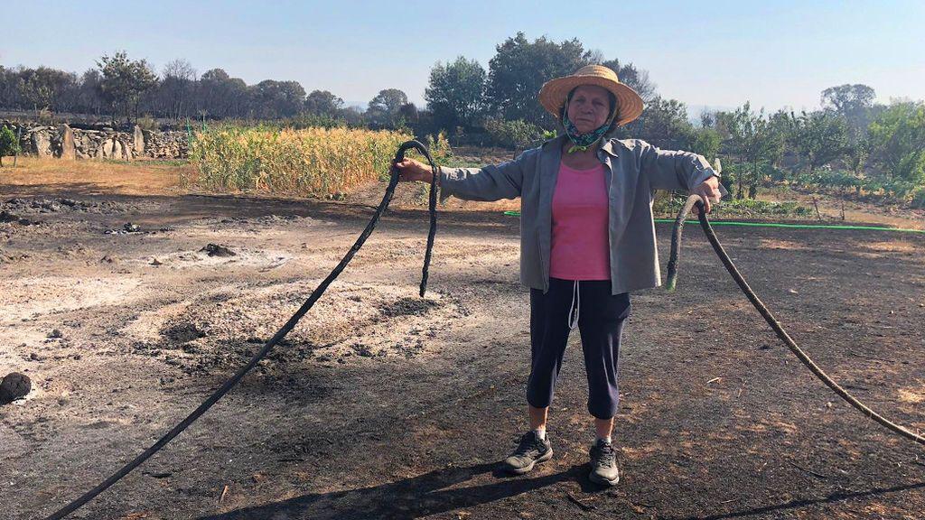 Angelita, en su finca, con los cultivos que se han salvado del fuego al fondo