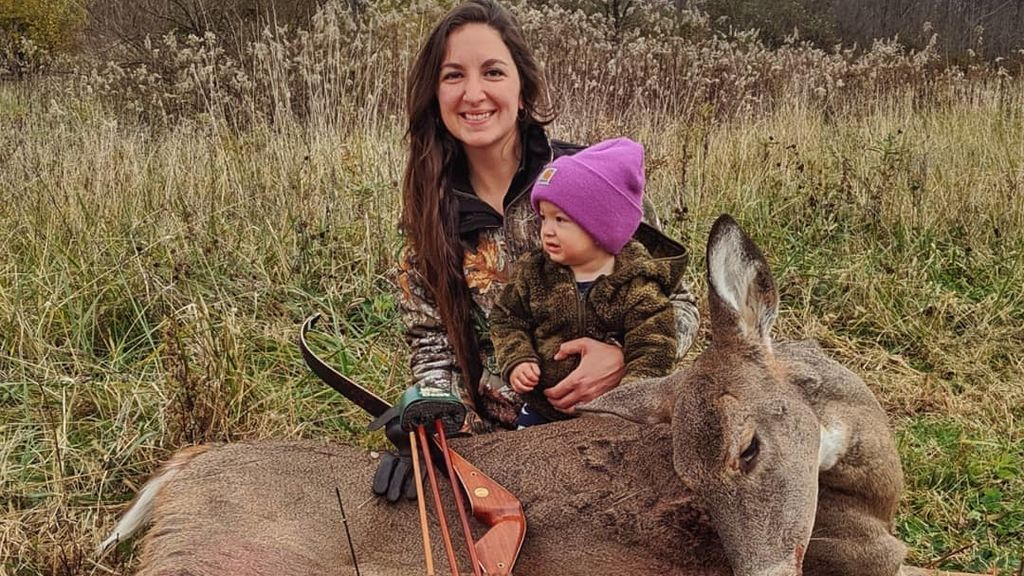 Beka Garris posando con un ciervo muerto y su hija de dos años