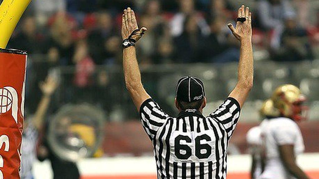árbitro marcando una falta durante un partido de fútbol americano