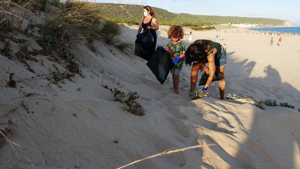 Voluntarios recogiendo basura en las dunas próximas al faro de Trafalgar
