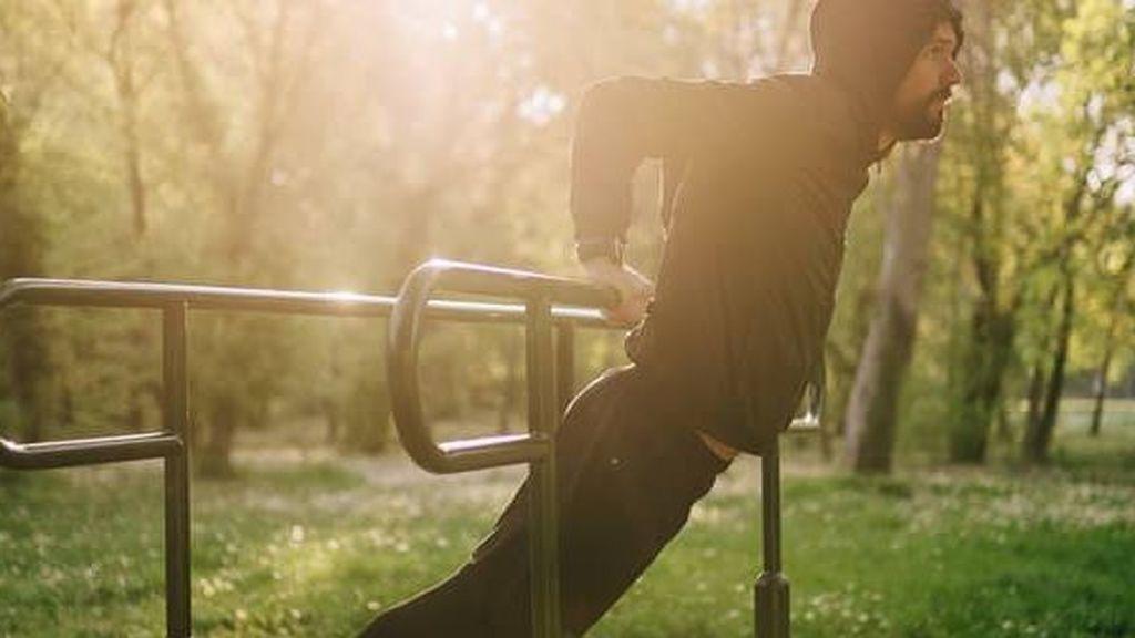 hombre entrenando calistenia en un parque de barras