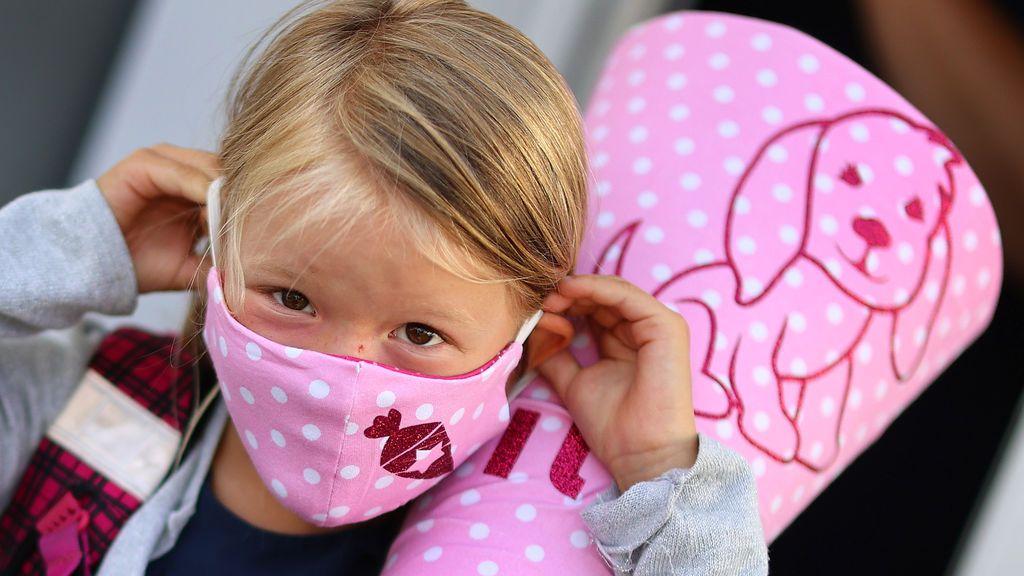 Una niña se coloca la mascarilla antes de regresar al colegio en Aleamia tras el confinamiento