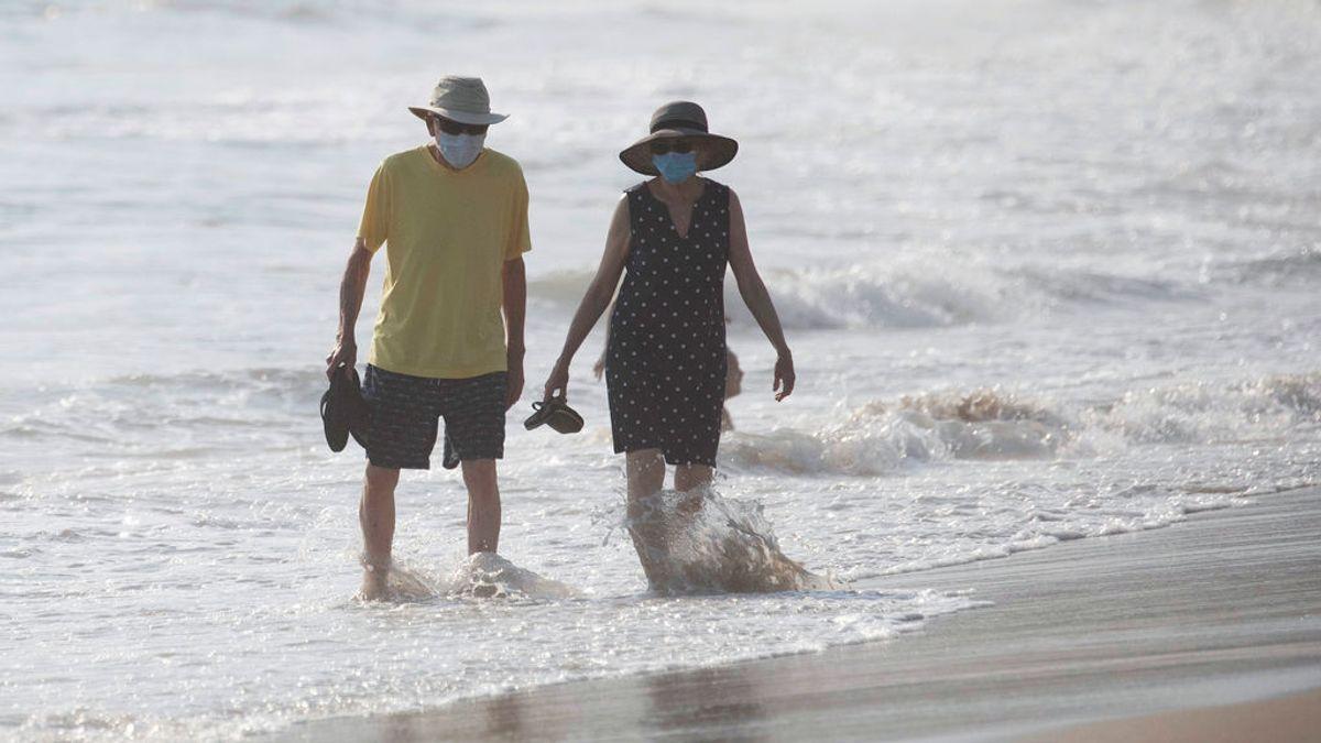 Dos personas pasean por una playa de California con mascarillas