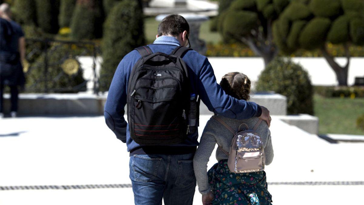 Un padre y su hija caminan al colegio