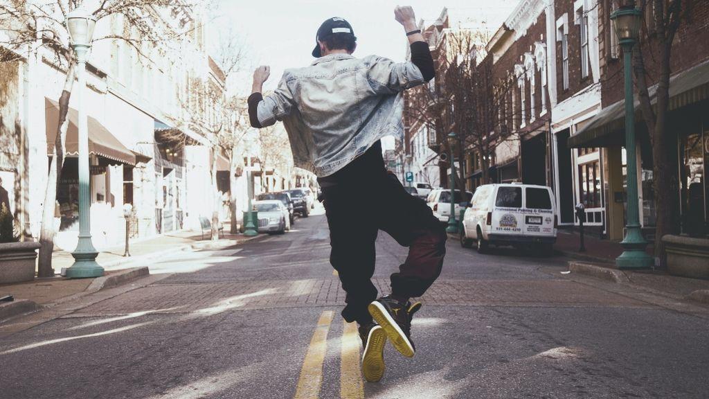 Un chico saltando libre y feliz por la calle