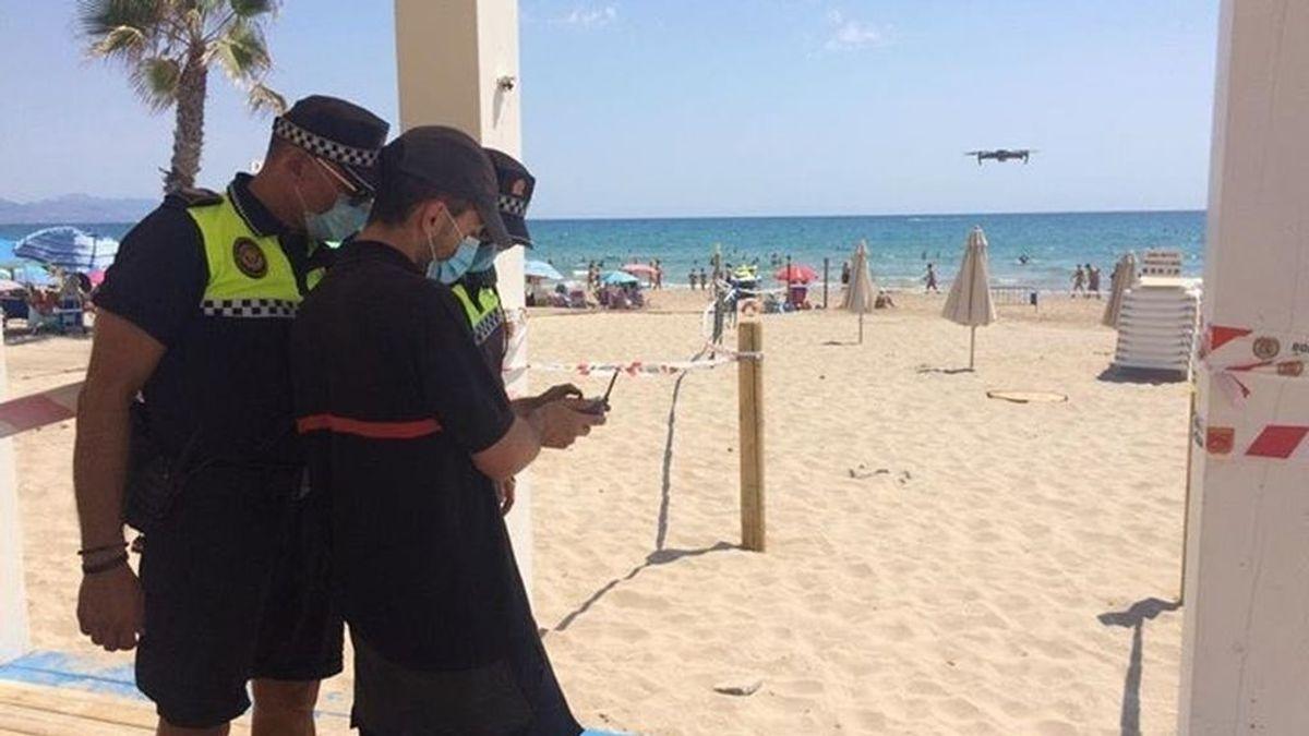 Desalojan de madrugada a 200 jóvenes en la playa del Postiguet de Alicante con un cadena humana de policías