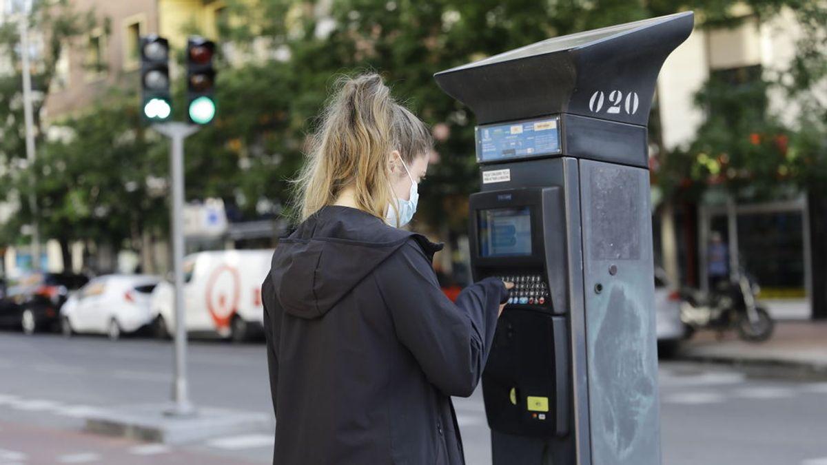 Una joven utiliza un parquímetro del Servicio de Estacionamiento Regulado (SER) de Madrid.