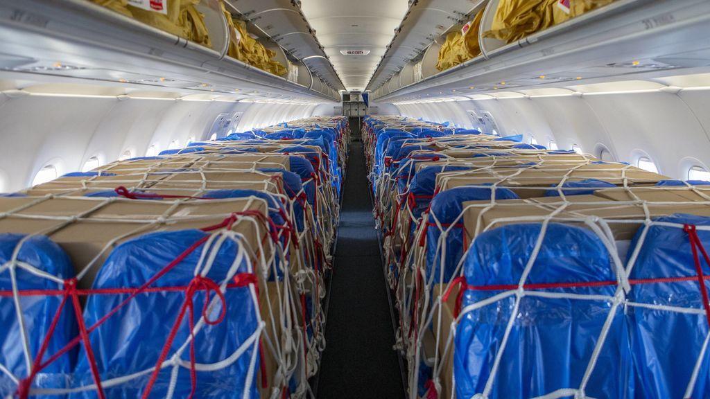 Carga de material sanitario apilada entre los asientos de la cabina