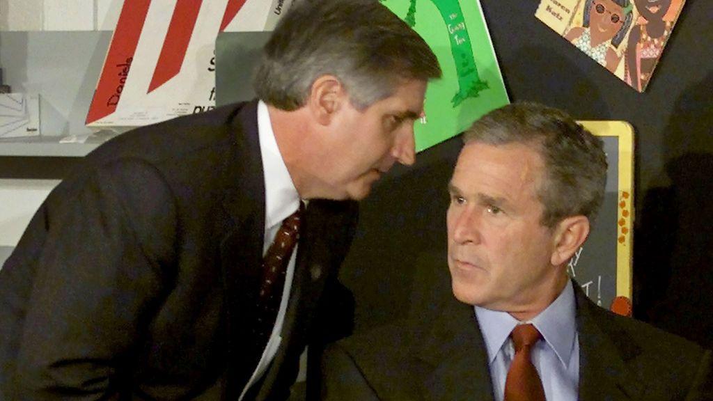 El presidente de EE.UU. George W. Bush escucha mientras el jefe de gabinete de la Casa Blanca Andrew Card le informa del impacto de un segundo avión.