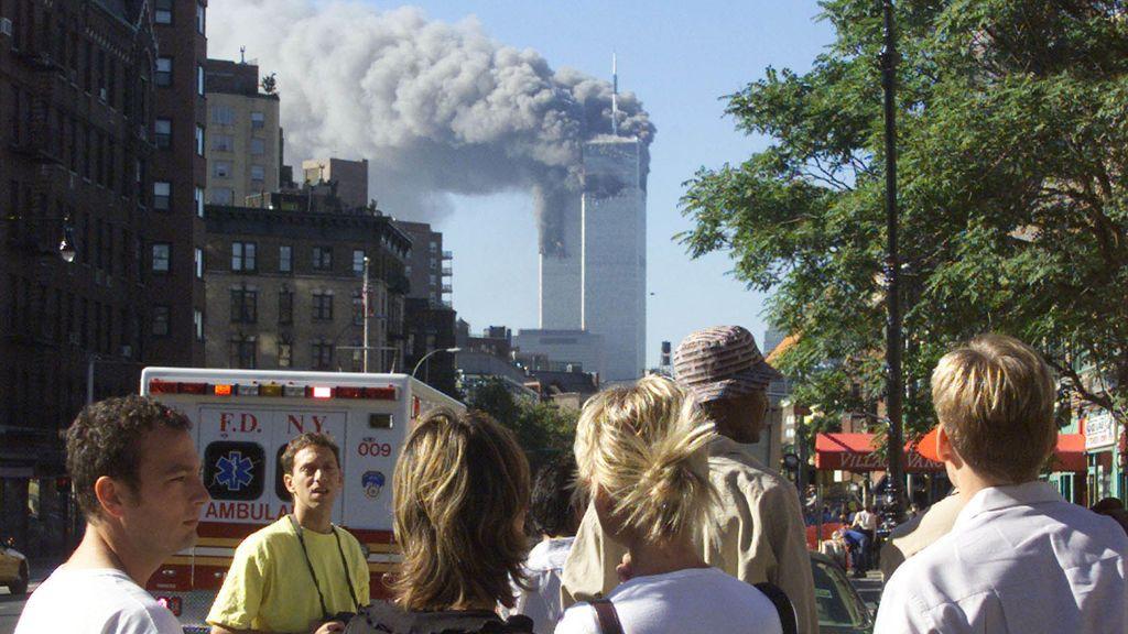 La gente observa las columnas de humo de las dos torres del World Trade Center.