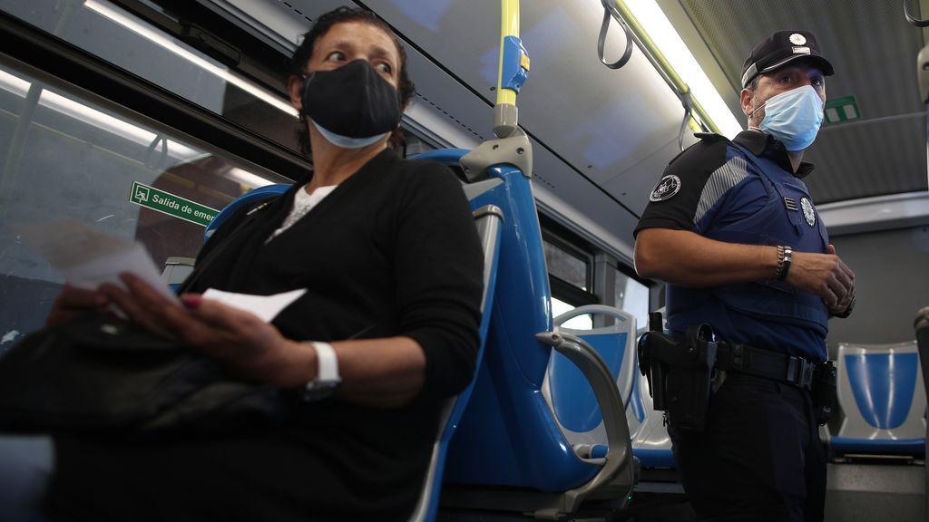 Un agente de la Policía Municipal de Madrid realiza un control de movilidad en una línea de autobús que pasar por el distrito de Puente de Vallecas, Madrid