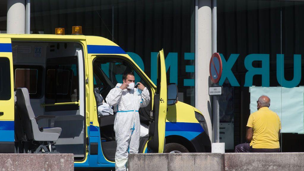 Un profesional sanitario baja de la ambulancia en la que viaja un paciente con coronavirus
