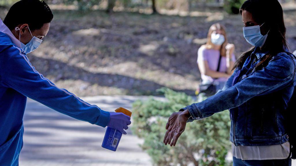 Un sanitario administra desinfectante a una mujer