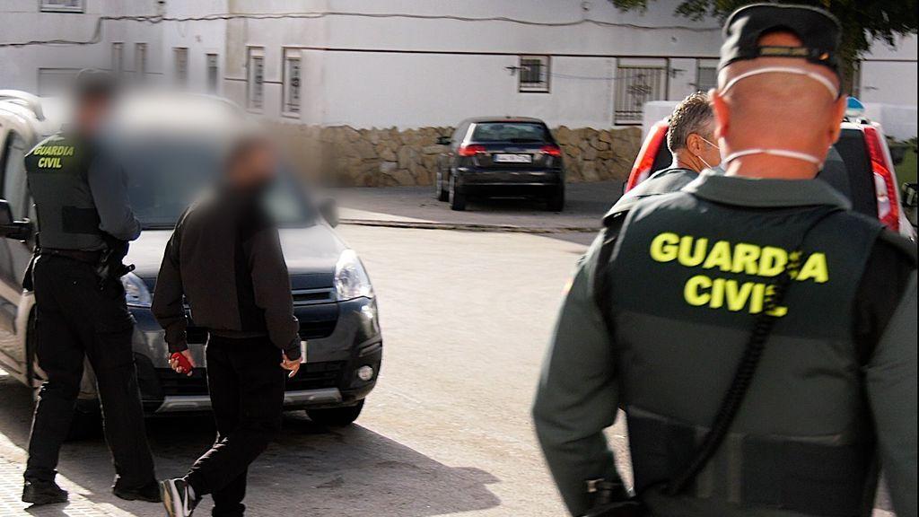 Dos guardias civiles flanquean a uno de los detenidos
