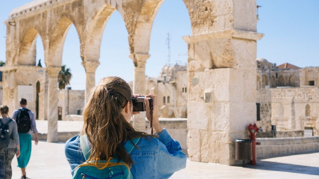 Una chica fotografiando el patrimonio monumental de Israel