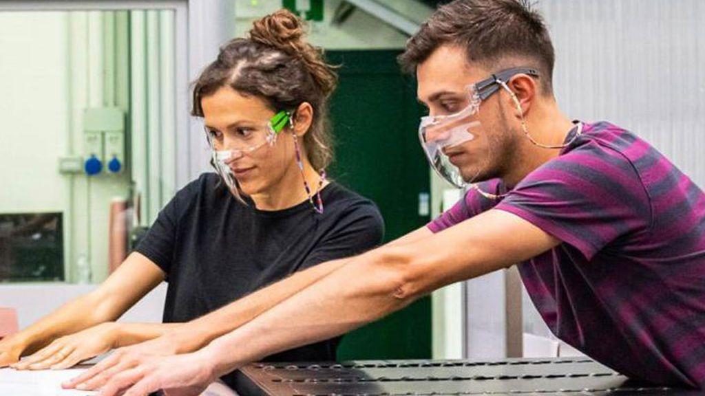 Dos trabajadores con mascarillas transparentes
