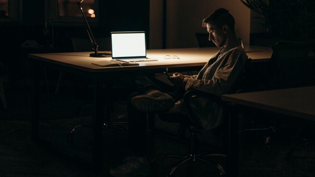 Un chico trabajando solo en la particular oficina de su casa al caer la noche