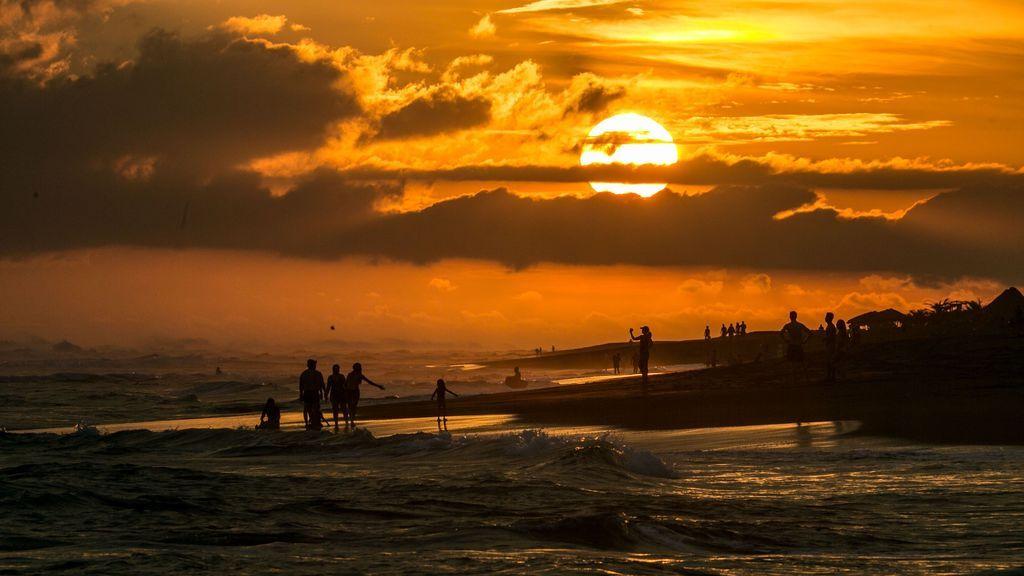 Turistas caminan junto al mar