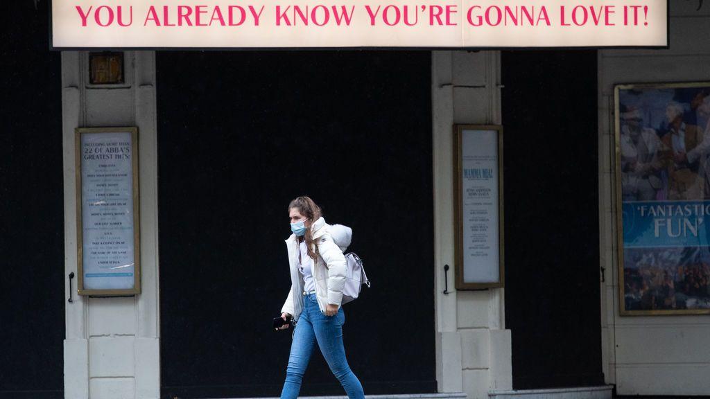 Mujer con mascarilla frente a un teatro en Londres