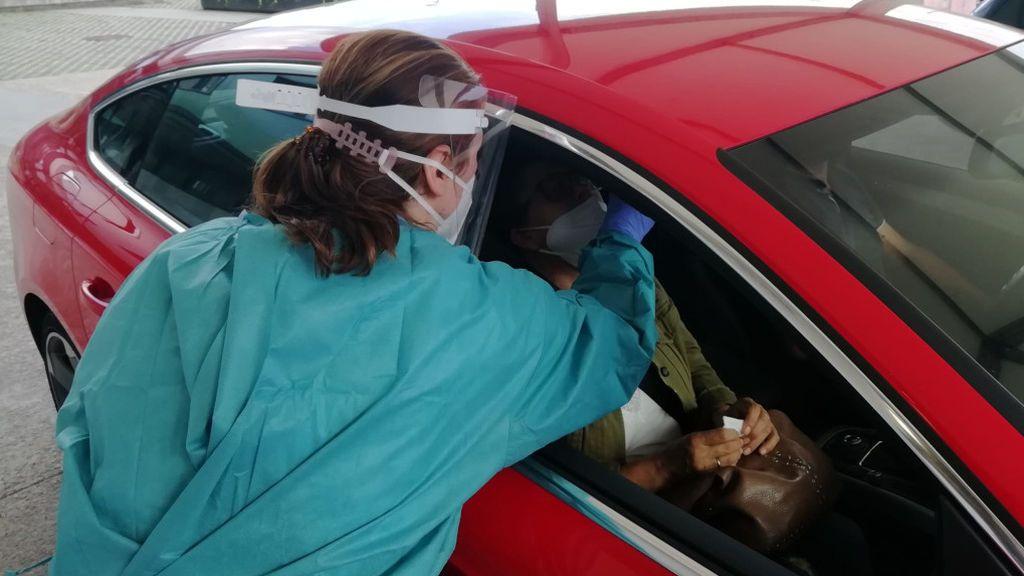 Una sanitaria toma una muestra a una mujer en un autocovid