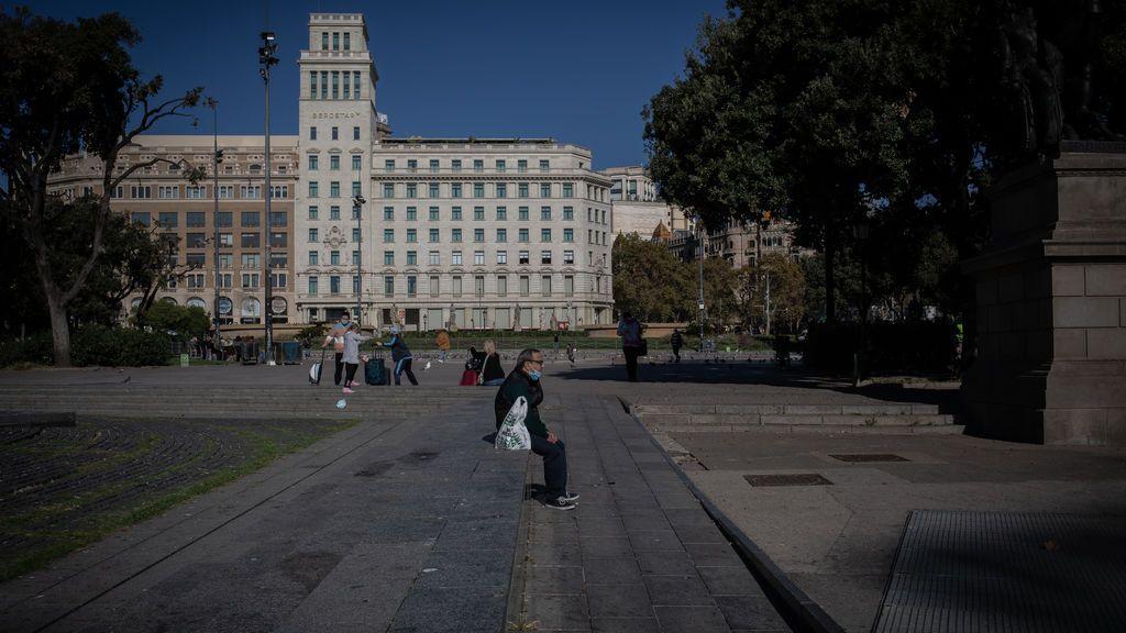 EuropaPress_3398352_hombre_sentado_plaza_cataluna_primera_manana_despues_toque_queda_barcelona