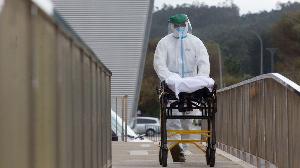 Un trabajador sanitario totalmente protegido traslada una camilla en las inmediaciones de la residencia de ancianos