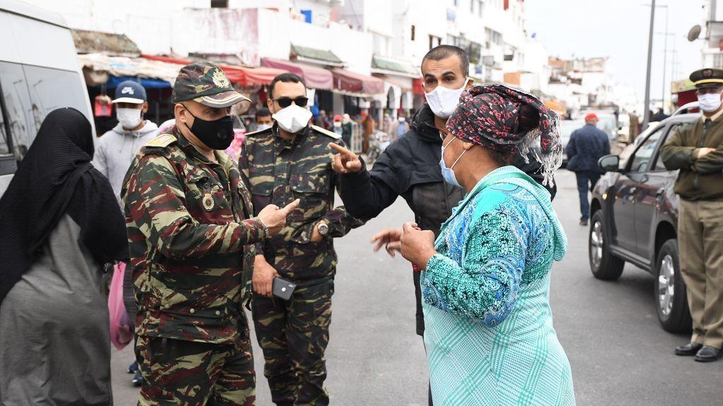 Miembros de las fuerzas de seguridad junto a otras personas con mascarilla en Rabat, Marruecos