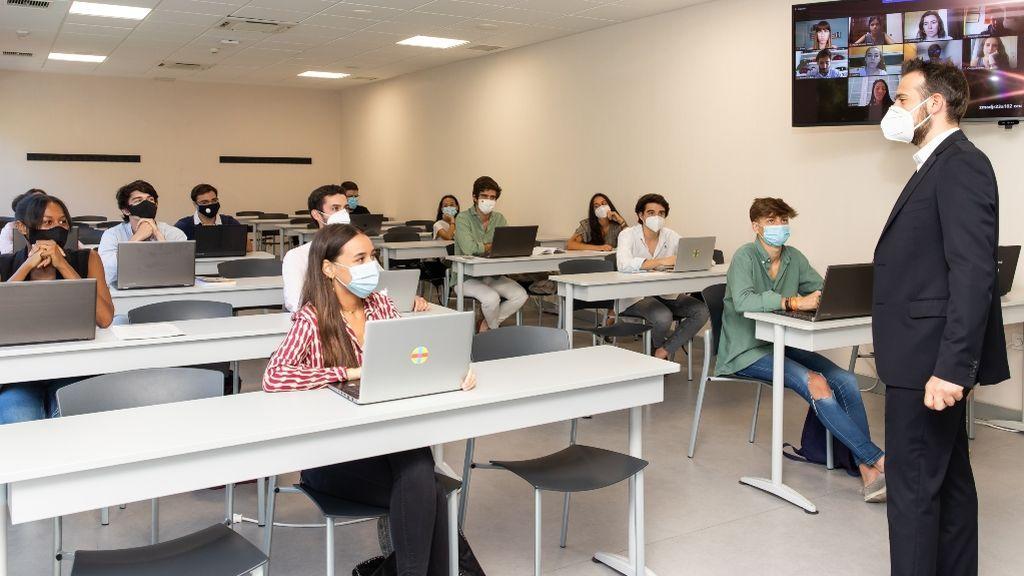 Un grupo de alumnos en una clase de universidad, cumpliendo con las normas