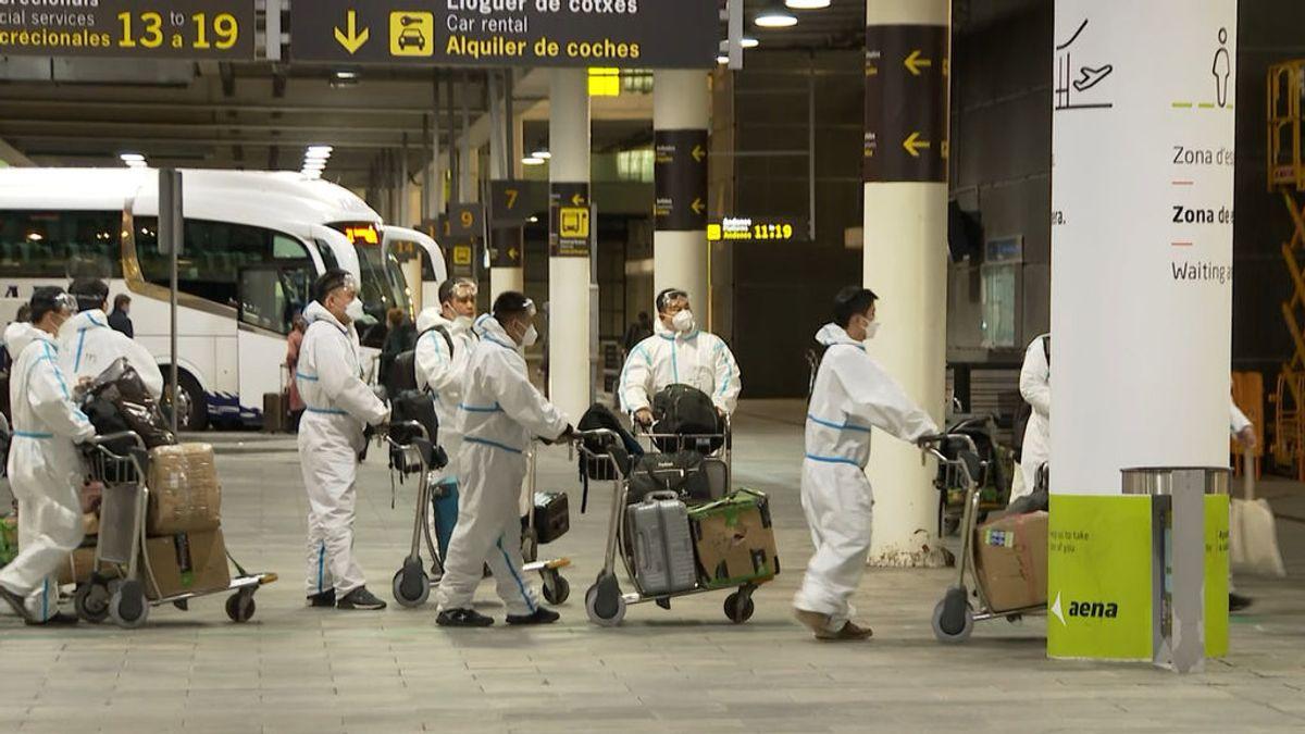 Con monos, guantes y mascarillas: así hacen escala en Barcelona un grupo de pasajeros chinos