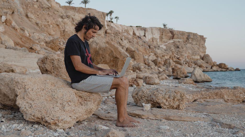 Un hombre trabajado con el ordenador desde la playa.
