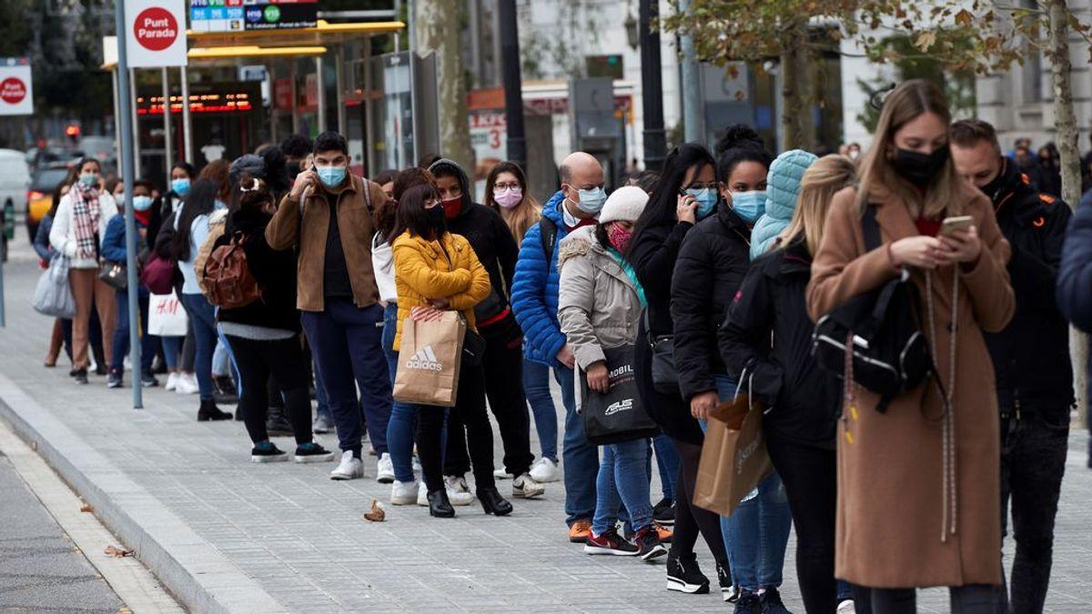 Numerosas personas hacen cola para entrar en una tienda de ropa en Barcelona
