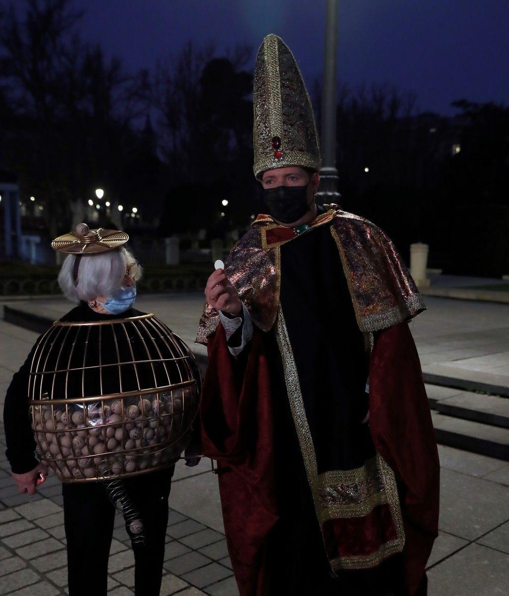 Dos entusiastas del Sorteo de Navidad disfrazados aguardan en las inmediaciones del Teatro Real