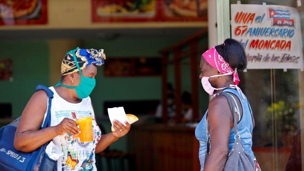 Dos mujeres protegidas con mascarilla hablan en una cafetería, en La Habana, (Cuba)