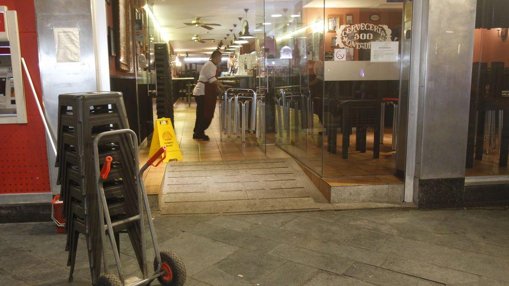 Un bar recoge las mesas tras una jornada laboral