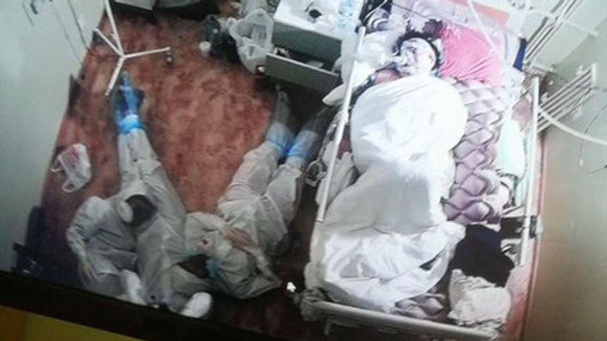 Tres sanitarios rusos se acuestan en el suelo tras una noche en vela junto a la cama de una paciente con covid