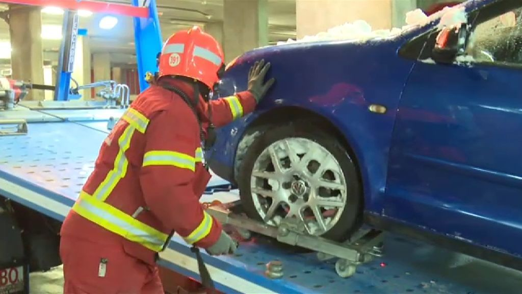 Operarios recogiendo coches abandonados por la nevada