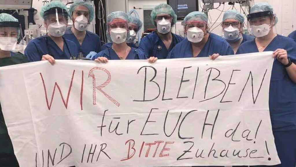 Equipo de sanitarios alemanes pidiendo a la población que se quede en casa.