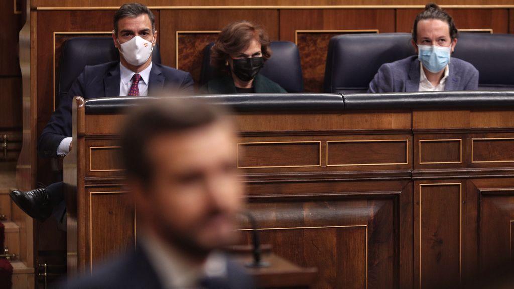 El presidente Pedro Sánchez y su vicepresidente Pablo Iglesias observan al líder del PP en el Congreso