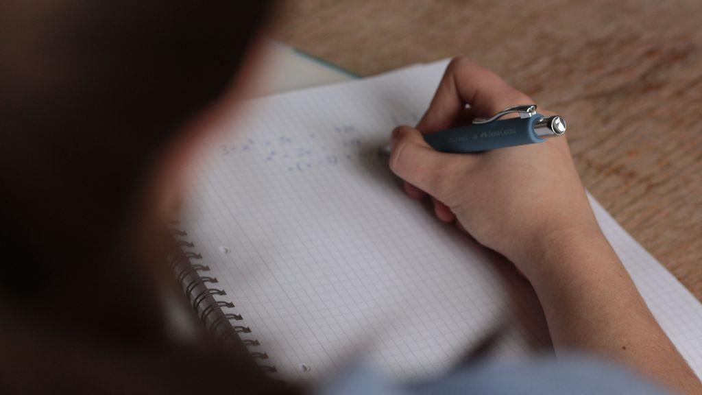 Un chico en clase escribiendo