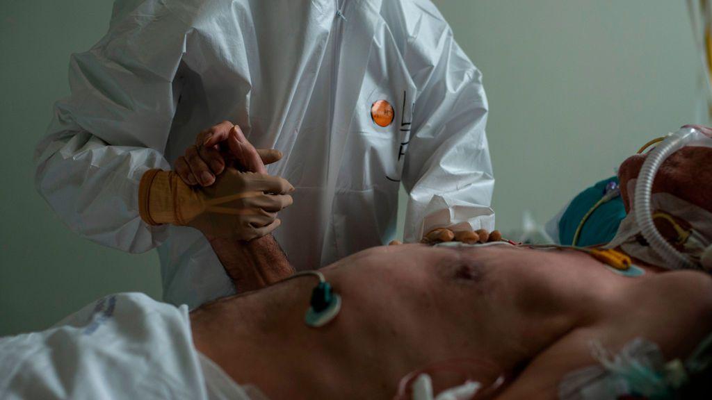 Un sanitario del Complejo Hospitalario Universitario de Ourense coge la mano a un paciente.