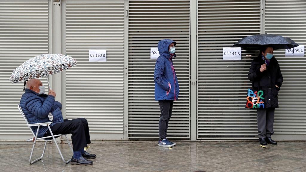 Varios votantes hacen cola en uno de los colegios electorales del Mercat de Sant Antoni de Barcelona